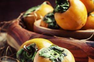 Fresh persimmons, vintage wooden bac