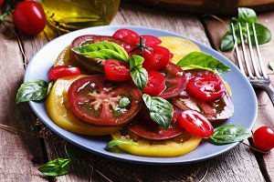 Salad of colorful tomatoes on plate.