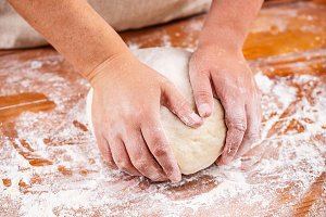 Female hands making bread dough