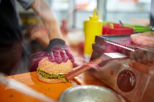 Chef in rubber gloves making burger