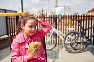 A girl is enjoying a cheese burger