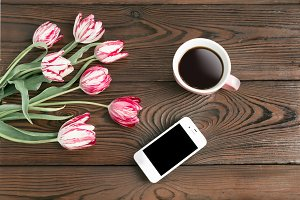 iPhone on a wooden table with flower