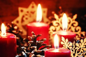 Burning red candles and pine cones w