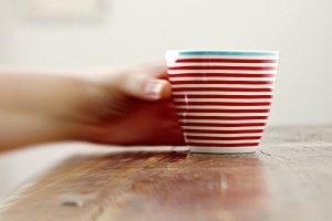 Blurry hand grabbing a striped mug