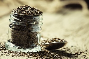 Caraway seeds in a glass jar and a s