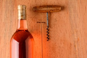Blush Wine and Corkscrew on Wood