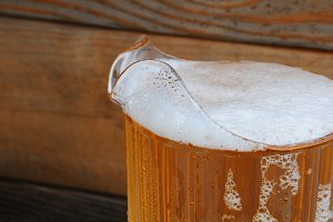 Closeup of Beer Pitcher with Wood Ba