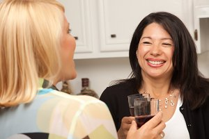 Two Girlfriends Enjoy Wine in the Ki