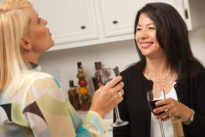 Two Girlfriends Enjoy Wine in the Ki