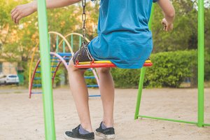 close up boys's legs sit on a swing