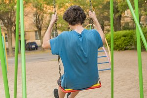 back view of teenager boy swinging o