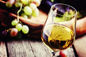 White wine in a glass with fall grap