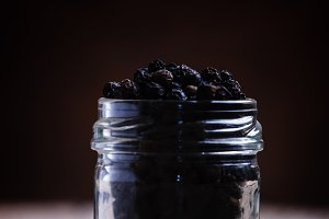 Pea of black pepper in a glass jar.
