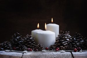 White burning candle with pine cones