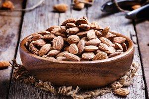 Raw peeled almond, vintage wooden ba