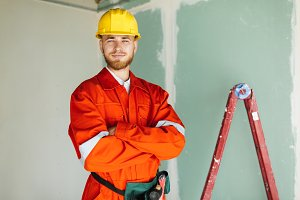 Young smiling builder in orange work