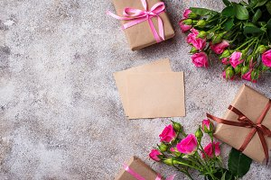Pink roses, gift boxes and greeting