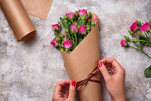 Womens hands wrap a bouquet of roses