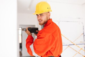 Young foreman in orange work clothes