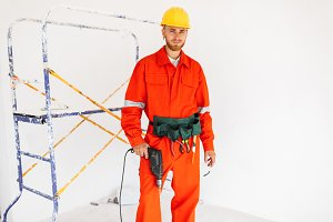 Young builder in orange work clothes