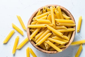 Pasta penne  in wooden bowl on whit