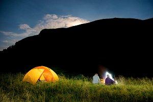 People near illuminated orange tent
