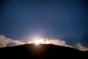 Raising of full moon above mountain