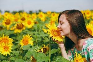 Brunette girl sniffing a sunflower i