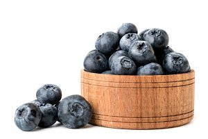 Ripe blueberries in a wooden plate