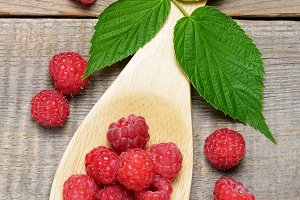 Raspberry in wooden spoon top view