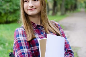 Teen girl outdoor holding books