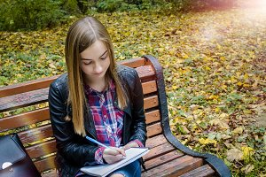 Teen girl reading a book at park