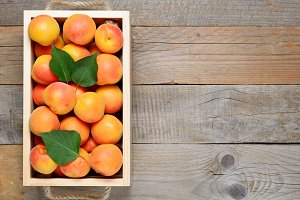 Apricots in box on wooden table