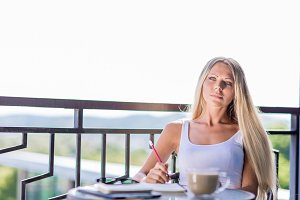 Young woman drink coffee and writing