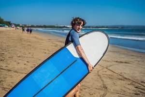 Handsome sporty young surfer posing