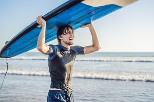 Man carrying surfboard over his head