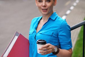 Girl with folders for papers, coffee