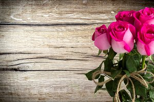 pink bouquet of roses on a wooden ba