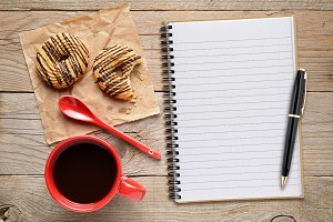 Coffee cup with cookies and notepad