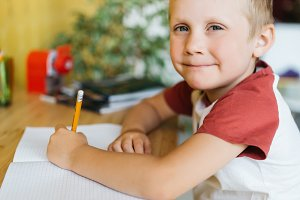 Photo of boy with pen and notebook
