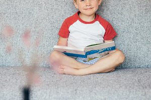 Photo of boy sitting with book on