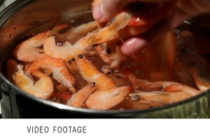 Shrimp are simmered in a saucepan.