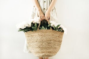 Peony flowers in straw bag