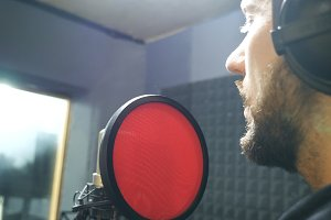 Male singer with beard in headphones
