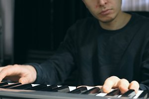 Male musician playing at synthesizer