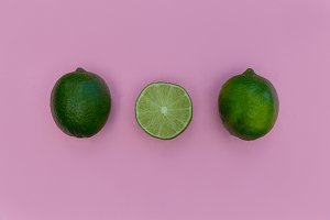Row of lime fruit pink background