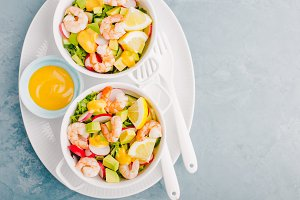 Salad with prawns in bowls on table