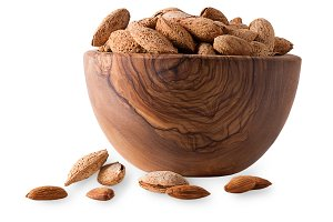 Wooden bowl full of almonds with she