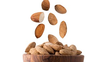 Isolated flying almond nuts in a woo