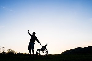 A young man standing by wheelchair